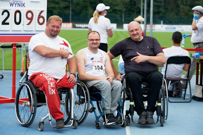 trzech zawodników na wózkach, dwóch po bokach wskazuje palcami na siedzącego centralnie, wszyscy uśmiechnięci